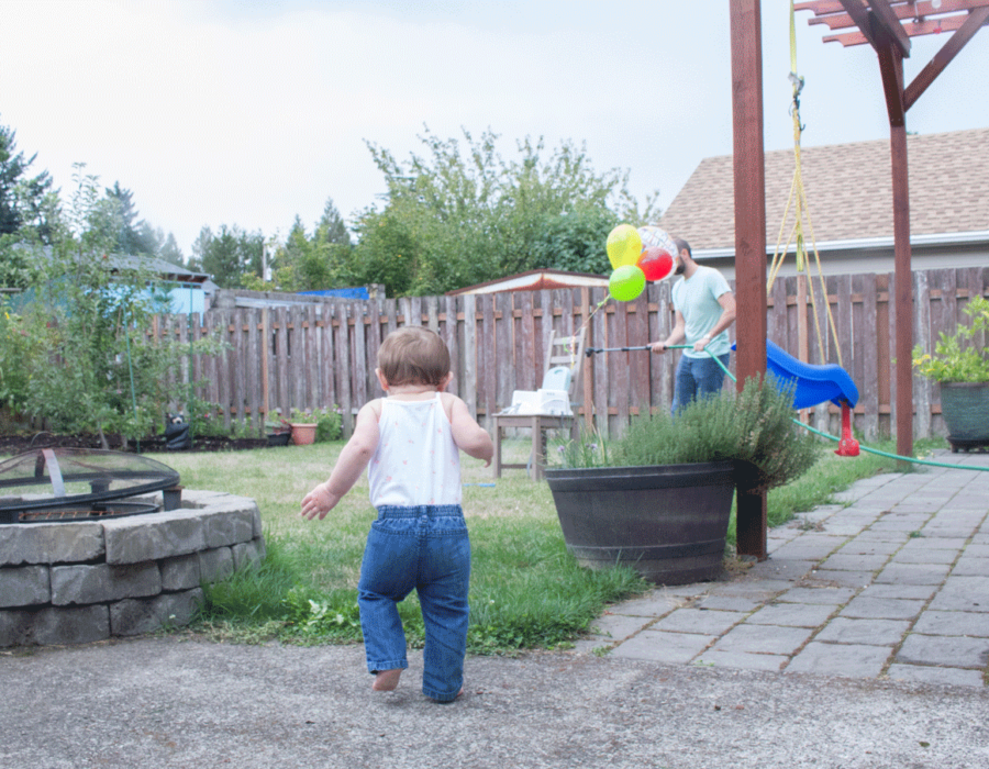 first-birthday-baby-running-towards-balloons-outside-firepit-lawn