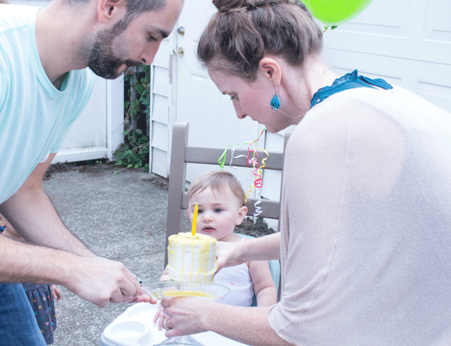first-birthday-parents-serving-baby-yellow-and-white-cake